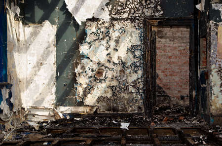 Grungy old building with burnt wooden floors and walls and peeling paint