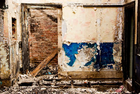 Interior of a old grungy building with burnt wooden planks and peeling paint