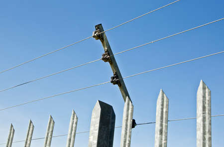 a galvanized fence holding a high voltage electric security fence