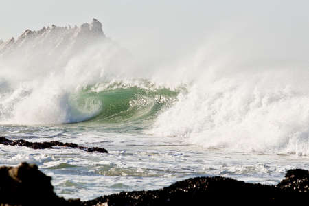 wind blowing: Strong wind blowing sea spray off a big wave with rocks behind and in front Stock Photo
