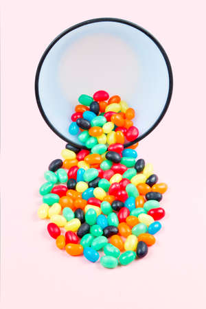 brightly: Brightly colored jelly bean candy being poured out of a bowl on a soft pastel pink background