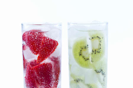 Two ready to drink glasses filled with strawberries and kiwis filled with ice on a white background