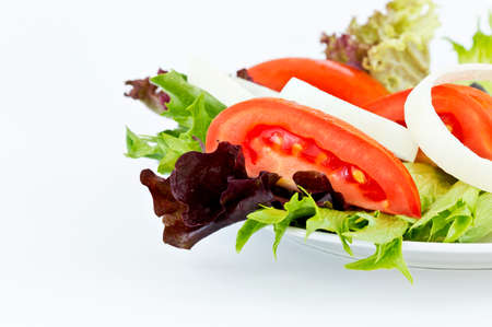 rocket lettuce: healthy salad made of tomatoes,onions,lettuce on a plate isolated on a white background with copy space