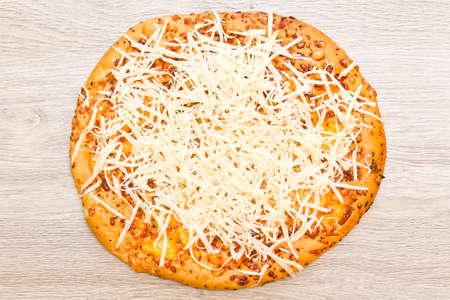 grated mozzarella cheese: Round whole pizza with freshly grated mozzarella cheese on top
