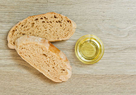 extra virgin: two slices of Ciabatta bread and a bowl of extra virgin oil on a wooden textured background