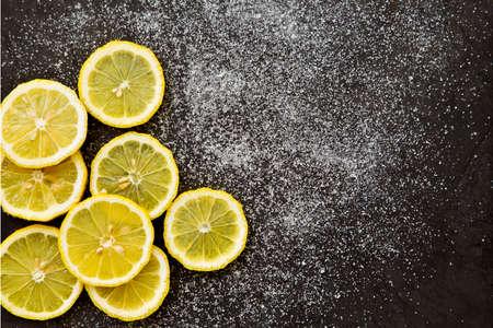 sweet segments: sliced lemons with sprinkled sugar on a dark grey background