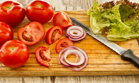 red onions: Salad ingredients including tomatoes,red onions,lettuce and a sharp cutting knife on a wooden cutting board