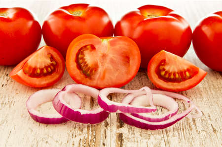 red onions: tasty ripe tomatoes with red onions on a white grainy wooden board Stock Photo