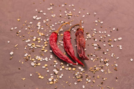 Three dried chilies and spices on a black background Stock Photo