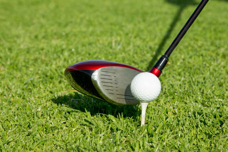Golf ball on a white tee in front of a driver on a lush green grass tee box