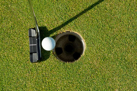 Golf putter used to putt the ball into the cup at close range Stock Photo