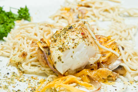 Piece of tasty white fish layed on noodles and cheese melted over the top