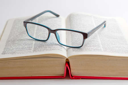 green coloured reading glasses placed on a book isolated on a white background