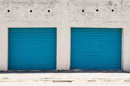 Two blue painted steel garage doors with peeling paint and dirty white walls surrounding them Stock Photo