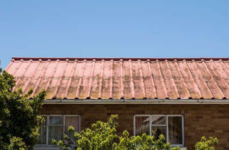 old asbestos roof covered in moss and dirt in the open sky on a sunny day Stock Photo
