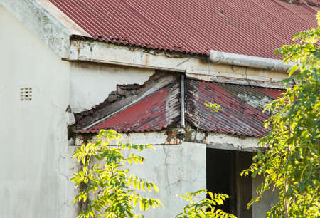 abandoned house with rusted iron roof sheets,cracked walls,and overgrown garden Stock Photo