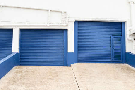 two blue storage gates for trucks with angled ramps -commercial building Stock Photo