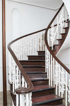 Spiral stair case in colonial style with steps and hand rails made from dark wood