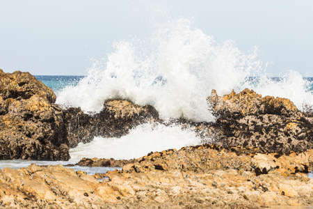 Waves breaking over rocks on a warm sunny day at the coast in Nelson Mandela bay