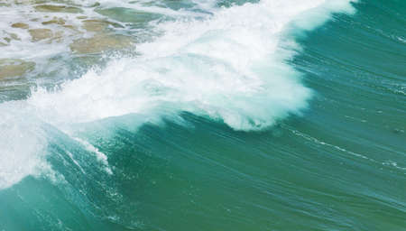back of a dramatic wave as it hits the sandy shore on a hot summers day Stock Photo