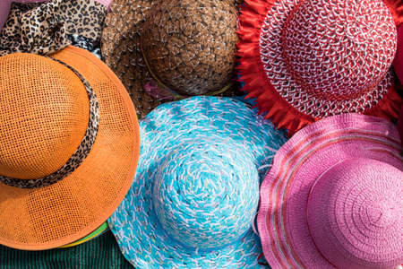 Brightly colored hats for sale at a market on a tropical beach