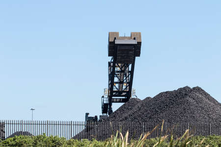 Coal dumps with working machinery creating huge dump piles on a hot sunny day