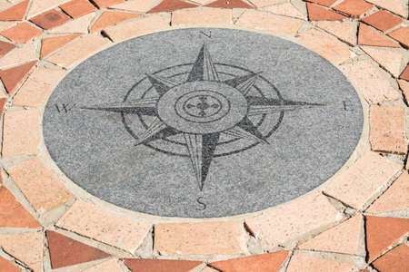 Compass showing north,south,east and west which has been built into brick a paving area