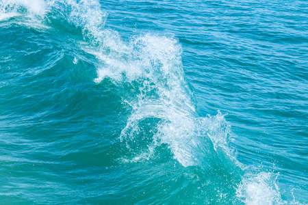Two waves collide off the coast of a tropical island on a hot sunny day