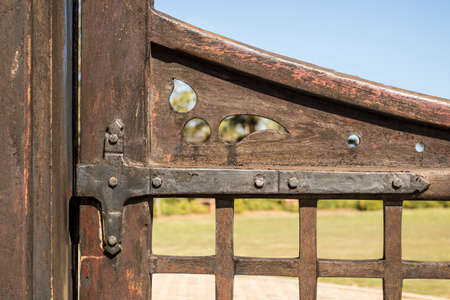 rusty old steel hinge holding a wooden gate on a post on a sunny day Stock Photo
