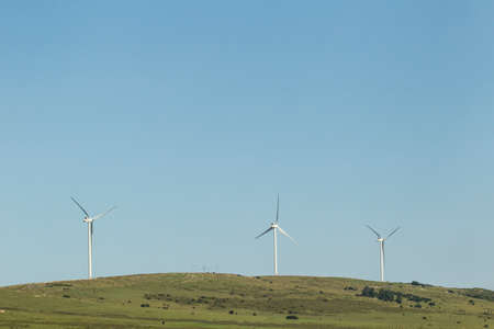 three large wind turbines on a hill producing power for the electricity grid on a sunny day Stock Photo