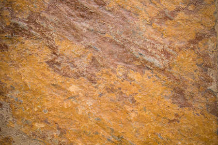 Orange rough textured stone background with stripes of brown rust