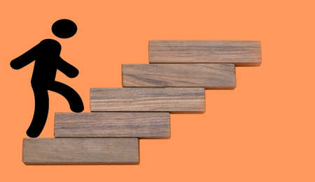person climbing wooden stairs to the top concept on a orange background
