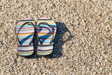 Pair of beach sandals with stripes lying on a stony beach beach early on a sunny morning
