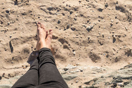 crossed feet in a relaxed position on soft beach sand and rocks Stock Photo