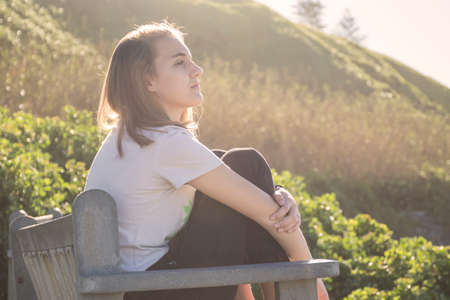 young woman sitting on a bench at the beach looking into the air early in the morning in bright sunlight