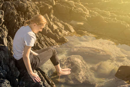 Young woman sitting on rocks looking into a pool of water at sunrise Stock Photo