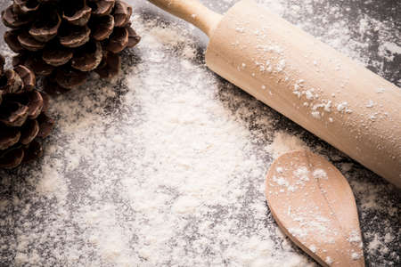 Baking concept of flour,rolling pin, wooden spoon and pine cones used for background with copy space