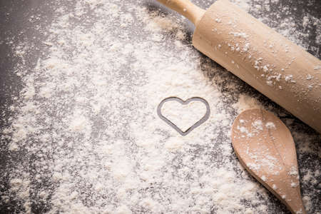 Baking background with heart shape in the flour with a rolling pin and spoon Stock Photo