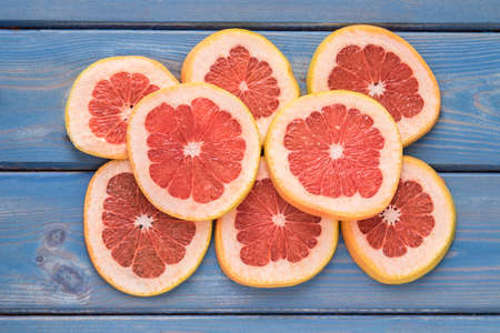 Juicy sweet Grapefruit sliced on a blue wooden background from above Stock Photo