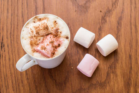White mug holding a hot drink with marshmallows on a wooden background