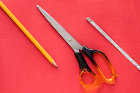 Items of stationery placed on a red background taken from above scissors,pencil,measuring tape