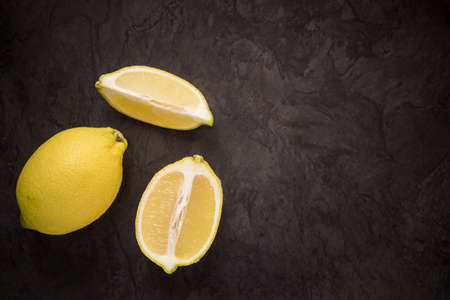 Lemons on a dark slate looking background from above