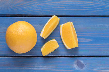 soft and juicy orange and slices on a blue wooden background Stock Photo