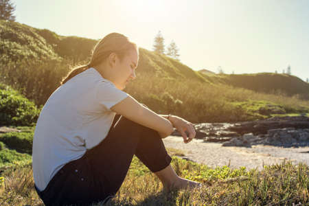 young woman sitting and relaxing in soft morning sun on wild grass next to the beach at low tide Stock Photo