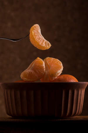 sliced naartjie or tangerine being lifted out of a bowl with a small metal fork photographed in a dark food style