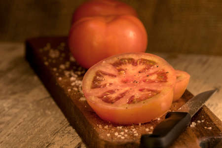 Spicy sliced tomato on a wooden board in soft window light photographed in a darkfood style Stock Photo