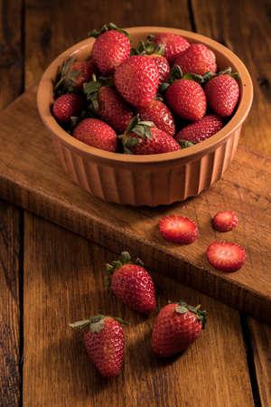 Sweet fresh strawberries in a Earthen bowl on a wooden board