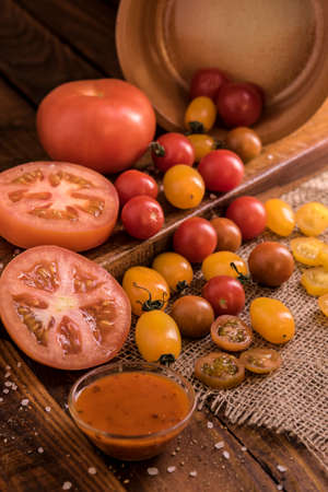 tomatoes spreading out on a wooden board in warm window light photographed in a dark food style Stock Photo