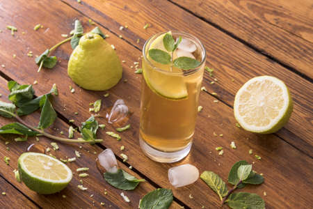 Fresh iced tea with lemons and ice cubes on a wooden board in soft window light Stock Photo