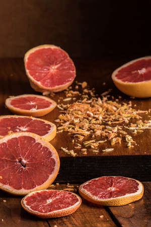Sliced grapefruit with grated peels on a wooden board with selective lighting Stock Photo